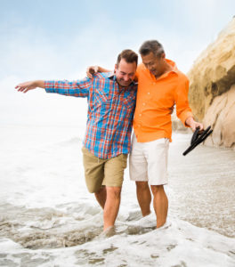 Gay couple walking on the beach